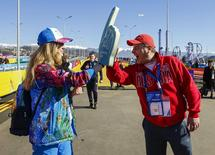 A fan (R) greets Yuliya Udalykh, a volunteer from the Urals city of Yekaterinburg, at the entrance to the Olympic Park during the Sochi 2014 Winter Olympics Games February 13, 2014. REUTERS/Shamil Zhumatov