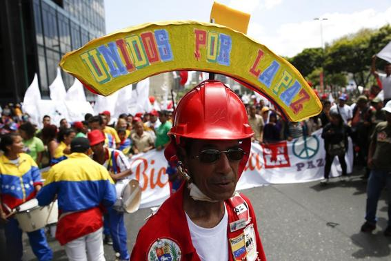 A supporter of Venezuelan President Nicolas Maduro attends a march in support of the government and to call for peace after the recent deadly violence following street protests, in Caracas February 15, 2014. REUTERS-Carlos Garcia Rawlins
