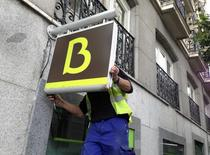 A worker puts in place a Bankia logo at a Bankia branch in Madrid May 20, 2013. REUTERS/Juan Medina