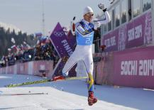 Sweden's Marcus Hellner celebrates after crossing the finish line during the men's cross-country 4 x 10km relay event at the 2014 Sochi Winter Olympics February 16, 2014. REUTERS/Carlos Barria