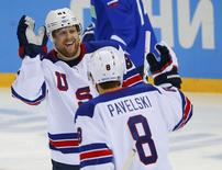 Team USA's Phil Kessel is congratulated by teammate Joe Pavelski after scoring on Slovenia during the first period of their men's preliminary round ice hockey game at the 2014 Sochi Winter Olympics, February 16, 2014. REUTERS/Brian Snyder