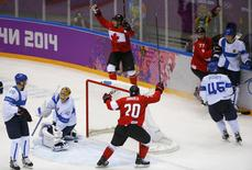 Canada's Drew Doughty (rear) celebrates after scoring the game winning overtime goal against Finland's goalie Tuukka Rask (40) with Canada's John Tavares (20) and Jeff Carter (77) as Finland's Lauri Korpikoski (L) and Finland's Sami Vatanen react during the overtime period of their men's preliminary round ice hockey game at the Sochi 2014 Winter Olympic Games February 16, 2014. REUTERS/Brian Snyder