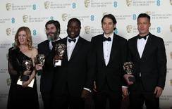 """Director Steve McQueen (C) celebrates with Dede Gardner (L-R), Anthony Katagas, Jeremy Kleiner and Brad Pitt after winning Best Film for """"12 Years a Slave"""" at the British Academy of Film and Arts (BAFTA) awards ceremony at the Royal Opera House in London February 16, 2014. REUTERS/Suzanne Plunkett"""