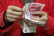 Клиент банка в китайском городе Суйнин считает юани 13 февраля 2010 года. Банки Китая выдали в январе рекордную сумму кредитов за четыре последних года, указывая на то, что вторая мировая экономика, возможно, замедляется не так быстро, как многие боятся. Однако более широкие индикаторы вселяют пессимизм. REUTERS/Stringer
