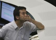 Сотрудник Токийской фондовой биржи изучает показания индексов во время торгов 13 июля 2012 года. Экономика Японии росла в конце прошлого года намного медленнее, чем ожидалось, бросая вызов регуляторам, поскольку, как оказалось, масштабные государственные стимулы не смогли подстегнуть потребление и экспорт. REUTERS/Toru Hanai