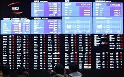 Люди смотрят на экран с котировками на Токийской фондовой бирже 14 февраля 2013 года. Азиатские фондовые рынки выросли в понедельник за счет хорошей экономической статистики Китая и местных новостей. REUTERS/Yuya Shino