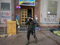 Антиправительственный демонстрант покидает здание мэрии в Киеве 16 февраля 2014. Украинские власти и оппозиция отвели силы от линии фронта, выполнив в срок условия перемирия, и собирают союзников для очередного витка противостояния - парламентской битвы за изменение Конституции и досрочные выборы президента с усечёнными полномочиями. REUTERS/Gleb Garanich