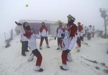 Canada's Christopher Robanske and compatriot Kevin Hill play with a tennis ball as they wait for the start of the men's snowboarding cross qualification round during a delay because of the fog at the 2014 Sochi Winter Olympic Games in Rosa Khutor, February 17, 2014. REUTERS/Mike Blake