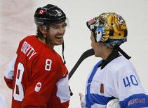 Canada's Drew Doughty laughs with Finland's goalie Tuukka Rask after Canada defeated Finland in overtime in their men's preliminary round ice hockey game at the 2014 Sochi Winter Olympics, February 16, 2014. REUTERS/Brian Snyder