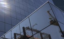 Um trabalhador e uma bandeira do Brasil em um canteiro de obras são refletidos na parede de um prédio comercial, na Avenida Paulista. As ações da Brookfield disparavam na manhã desta segunda-feira, na maior alta do Ibovespa, após sua controladora ter anunciado uma oferta pública de aquisição de ações para tirar a incorporadora da bolsa. 29/08/2013 REUTERS/Nacho Doce