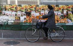 Una mujer pasa en bicicleta junto a una verdulería en Tokio, feb 17 2014. La economía de Japón creció a un ritmo mucho más lento que lo esperado a fines del año pasado, lo que representa un reto para los funcionarios en momentos en que los esfuerzos de estímulo del Gobierno muestran pocas señales de haber desatado un impulso del consumo y las exportaciones. REUTERS/Yuya Shino