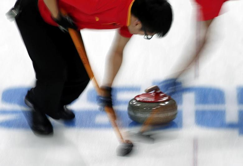 China's third Xu Xiaoming sweeps ahead of a stone during their men's curling round robin game against Britain at the Ice Cube Curling Center during the 2014 Sochi Winter Olympics February 17, 2014. REUTERS/Marko Djurica