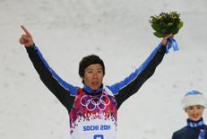 China's third placed Jia Zongyang celebrates on podium after the men's freestyle skiing aerials finals at the 2014 Sochi Winter Olympic Games in Rosa Khutor February 17, 2014. REUTERS/Mike Blake