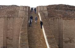 People stand on the steps of the Ziggurat of Ur ruins near Nassiriya, 300 km (186 miles) southeast of Baghdad, January 23, 2014. REUTERS/Ahmed Saad