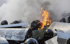 Бойцы внутренних войск пытаются справиться с огнём в противостоянии с антиправительственными демонстрантами в Киеве 18 февраля 2014 года. Противостояние демонстрантов и силовиков возобновилось в правительственном квартале в центре Киева во вторник после трехнедельного перемирия: милиция не позволила протестующим приблизиться к зданию парламента, где оппозиция требует урезать полномочия президента и провести досрочные выборы. REUTERS/Vlad Sodel