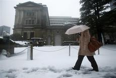 Una persona pasa frente al Banco de Japón en un día de invierno en Tokio, feb 15 2014. El Banco de Una persona pasa frente al Banco de Japón en un día nevado en Tokio, feb 15 2014. Japón mantuvo su política monetaria expansiva del martes y reiteró su opinión optimista sobre la economía, imperturbable ante las recientes señales de un crecimiento más lento y sugiriendo que cualquier estímulo adicional está lejos. REUTERS/Yuya Shino