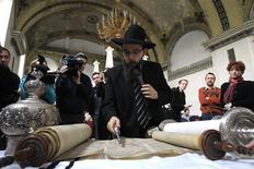 Rabbi Baruch Oberlander shows the media how a Torah is used in a synagogue during a news conference in Budapest February 18, 2014. REUTERS/Bernadett Szabo