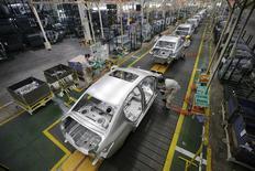 Dans une usine Dongfeng Peugeot Citroën à Wuhan, dans la province chinoise de Hubei. Selon des sources proches du dossier, PSA Peugeot Citroën et le chinois Dongfeng Motor ont signé mardi le protocole d'accord qui doit donner une dimension capitalistique à leur partenariat industriel. /Photo prise le 13 février 2014/REUTERS/Darley Shen