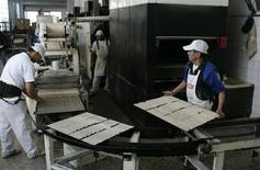 Unos obreros en la fábrica de palitos de pan Grissinopoli en Buenos Aires, sep 15 2011. La economía de Argentina se habría expandido apenas un pobre 1,4 por ciento interanual en diciembre, a su menor ritmo en el año afectada principalmente por una fuerte caída en la producción industrial, de acuerdo a un sondeo de Reuters difundido el martes. REUTERS/Martin Acosta