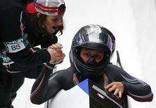 Pilot Elana Myers (front) and Lauryn Williams of the U.S. are congratulated after completing a run in the women's bobsleigh event at the 2014 Sochi Winter Olympics, at the Sanki Sliding Center in Rosa Khutor February 18, 2014. REUTERS/Fabrizio Bensch