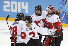 Canada's goalie Shannon Szabados (R) is congratulated by teammates Jocelyne Larocque (C), Laura Fortino (8) and Meghan Agosta-Marciano (2) after they defeated Switzerland in their women's ice hockey semi-final game at the Sochi 2014 Winter Olympic Games February 17, 2014. REUTERS/Jim Young
