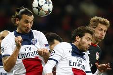 Paris St Germain's (L-R) Zlatan Ibrahimovic and Maxwell and Bayer Leverkusen's Stefan Kiessling jump for the ball during their Champions League soccer match in Leverkusen February 18, 2014. REUTERS/Ralph Orlowski