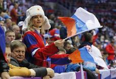 Болельщица с флагом России перед матчем хоккейных сборных России и Словакии на Играх в Сочи 16 февраля 2014 года. В среду на зимних Олимпийских играх в Сочи будут разыграны восемь комплектов медалей. REUTERS/Mark Blinch