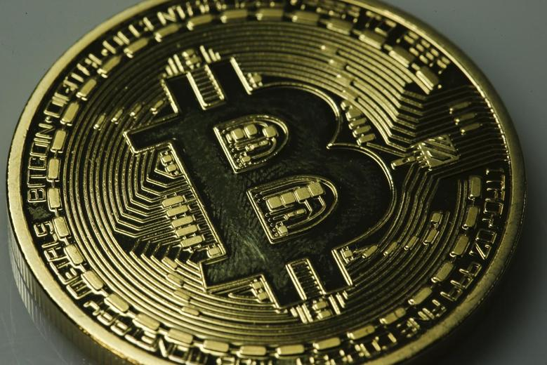 A mock Bitcoin is displayed on a table in an illustration picture taken in Berlin January 7, 2014. REUTERS/Pawel Kopczynski