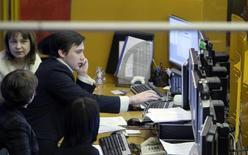 Люди за работой на бирже ММВБ в Москве 11 января 2009 года. Российский фондовый рынок в среду не нашел сил для продолжения роста, учитывая тревоги за судьбу рубля и Украины, а отчет Лукойла о сокращении прибыли в 2013 году оказал дополнительное давление на акции компании. REUTERS/Denis Sinyakov