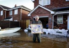 Builder Derek Bristow, 64, poses outside his house with one of the photos he will rescue first if the flood water rises any further in his house, in the flooded Somerset village of Moorland February 16, 2014. REUTERS/Cathal McNaughton