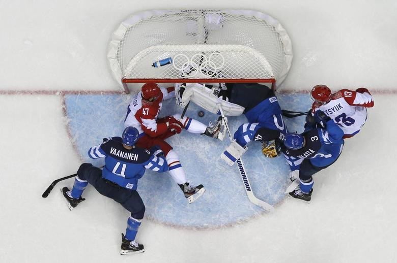 Russia's Alexander Radulov (47) tries to push the puck into the goal as Finland's goalie Tuukka Rask (3rd R) defends during the third period of their men's quarter-finals ice hockey game at the Sochi 2014 Winter Olympic Games February 19, 2014. REUTERS/Mark Blinch