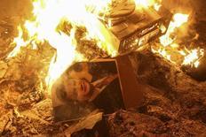 Портрет президента Украины Виктора Януковича горит в разрушенном здании спецслужб во Львове 19 февраля 2014 года. Противники президента Украины провозгласили политическую автономию в крупном городе на западе страны после ночи столкновений и стычек, которые привели к захвату административных зданий и вынудили полицию сдаться. REUTERS/Marian Striltsiv