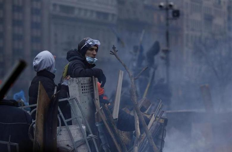 Anti-government protesters smoke at a barricade in central Kiev February 19, 2014. REUTERS/David Mdzinarishvili