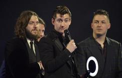 Alex Turner (C) of the Arctic Monkeys talks after being presented with the British Album award at the BRIT Awards, celebrating British pop music, at the O2 Arena in London February 19, 2014. Seen are Nick O'Malley (L) and Matt Helders (R). REUTERS/Toby Melville