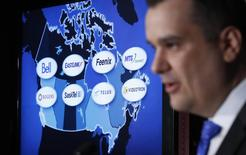 A screen displays the logos of Canadian telecom companies as Industry Minister James Moore speaks during a news conference in Ottawa February 19, 2014. REUTERS/Chris Wattie
