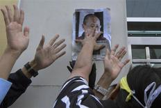 Pro-democracy activist Lui Yuk-lin posts a picture of Liu Xia, the wife of jailed Nobel Peace Prize Laureate Liu Xiaobo, on a wall during a protest calling for the freeing of Chinese dissidents outside the Chinese liaison office in Hong Kong in this December 5, 2013 file photo. REUTERS/Tyrone Siu/Files