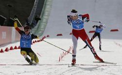 Норвежский двоеборец Йорген Гробак опережает на финише эстафеты немца Фабиана Риссле на Олимпиаде в Сочи 20 февраля 2014 года. Сборная Норвегии выиграла соревнования в лыжном двоеборье на Олимпийских играх в Сочи, команда России заняла последнее место. REUTERS/Stefan Wermuth