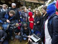 Russian punk band Pussy Riot members Maria Alyokhina (3rd R) and Nadezhda Tolokonnikova (2nd R) along with masked members show a video to journalists on a laptop computer during the 2014 Sochi Winter Olympics, in Adler February 20, 2014. REUTERS/Shamil Zhumatov