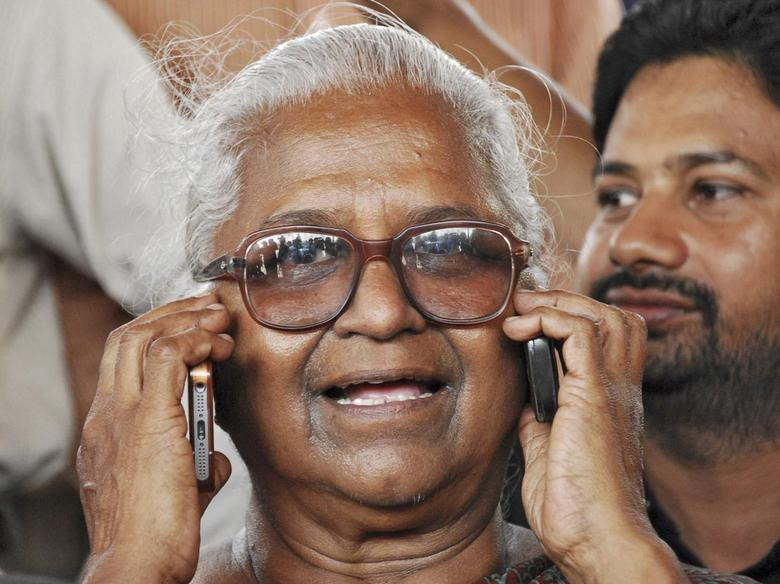 Arputhammal, mother of Perarivalan, one of the three men convicted for involvement in the killing of former prime minister Rajiv Gandhi, speaks on two mobile phones during celebrations after the Supreme Court commuted death sentences on the three men to life imprisonment, in the southern Indian city of Chennai February 18, 2014. REUTERS/Stringer