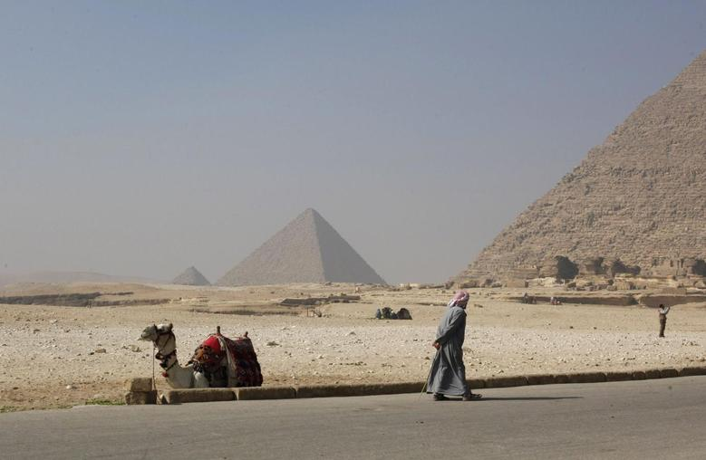 A worker walks near his camel as he waits for tourists at the Giza pyramids area, south of Cairo, February 20, 2014. REUTERS/Asmaa Waguih