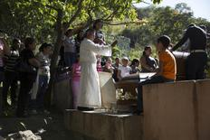 Atilio Gonzalez (C), a priest of the Southern Cemetery for the last 24 years, prays during a burial ceremony at the Southern Cemetery in Caracas January 28, 2014. REUTERS/Carlos Garcia Rawlins
