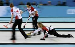 Canada's lead Dawn McEwen (L) and second Jill Officer prepare to sweep as skip Jennifer Jones (R) delivers a stone in their women's gold medal curling game against Sweden at the Ice Cube Curling Centre during the Sochi 2014 Winter Olympics February 20, 2014. REUTERS/Marko Djurica