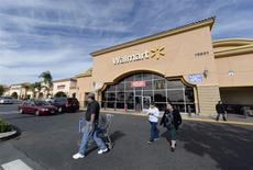 Unos clientes a las afueras de un supermercado de la cadena Walmart en Los Angeles, nov 26 2013. Wal-Mart Stores Inc pronosticó una utilidad para todo el año menor a la que esperan los analistas porque el recorte de beneficios gubernamentales, mayores impuestos y condiciones crediticias más estrictas erosionan sus ventas, y la noticia hacía caer sus acciones más de un 2 por ciento. REUTERS/Kevork Djansezian/Files