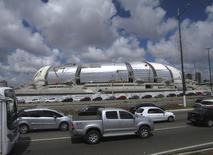 Carros passam na frente da Arena Das Dunas, em obras em preparação para a Copa do Mundo FIFA 2014 em Natal. O financiamento para compra de veículos no Brasil deve ter em 2014 o terceiro ano de queda ou estagnação, previu nesta quinta-feira a Associação Nacional das Empresas Financeiras das Montadoras (Anef). 13/12/2013 REUTERS/Gary Hershorn