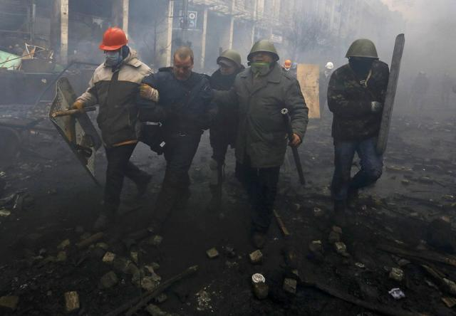 Anti-government protesters detain a policeman (2nd L) during clashes in the Independence Square in Kiev February 20, 2014. REUTERS/Yannis Behrakis
