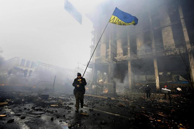 An anti-government protester holds a Ukranian flag as he advances through burning barricades in Kiev's Independence Square February 20, 2014. REUTERS/Yannis Behrakis