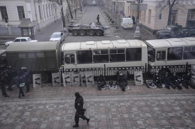 Interior ministry soldiers sit behind buses parked outside the parliament building in Kiev February 20, 2014. REUTERS/Andrew Kravchenko/Pool