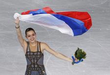Russia's Adelina Sotnikova celebrates holding her flag at the end of the Figure Skating Women's free skating Program at the Sochi 2014 Winter Olympics, February 20, 2014. REUTERS/Issei Kato