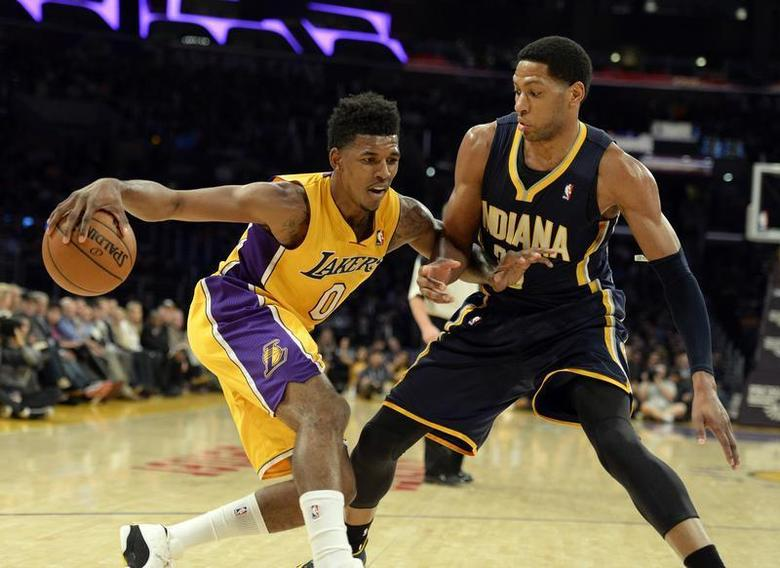 Jan 28, 2014; Los Angeles, CA, USA; Los Angeles Lakers small forward Nick Young (0) controls the ball against Indiana Pacers small forward Danny Granger (33) during the first half at Staples Center. Mandatory Credit: Richard Mackson-USA TODAY Sports - RTX17Z7H