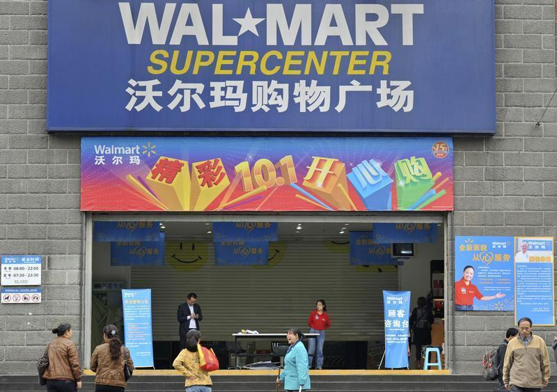 5c2b210cf5d Employees stand in front of the gate to a Wal-Mart Supercenter in Chongqing  municipality October 24